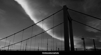 A dramatic dusk sky captures people crossing the Elizabeth Bridge