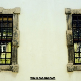 A pair of Castle Hill windows reflect the yellow building opposite