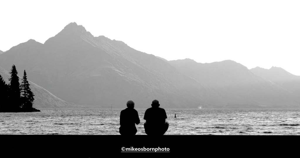 Two people relax by Lake Wakatipu, Queenstown, New Zealand