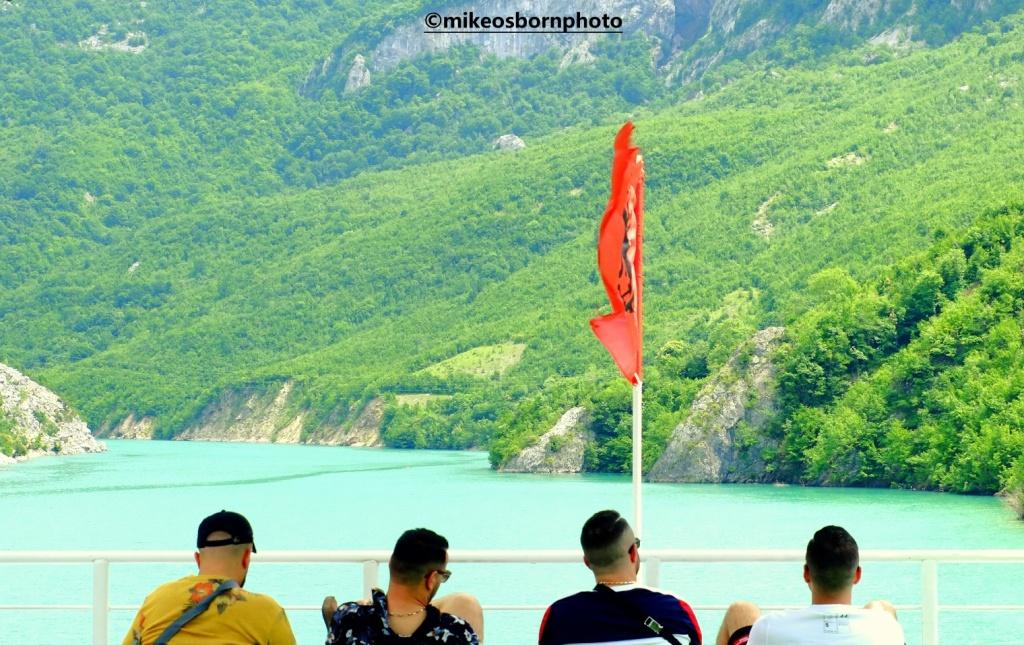 Four men on a boat at Lake Koman, Albania
