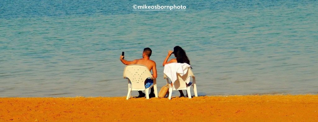 Couple taking selfies on the Dead Sea