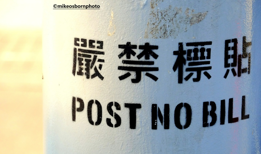 Pole stamped with 'post no bills' in Hong Kong