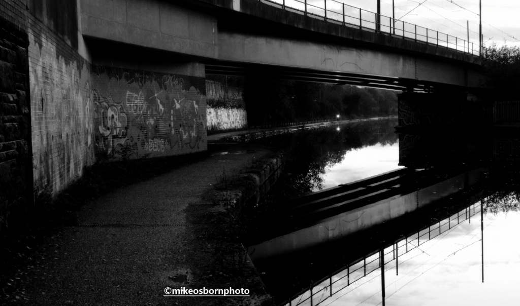 Cyclist approaches along Bridgewater Canal towpath, Manchester