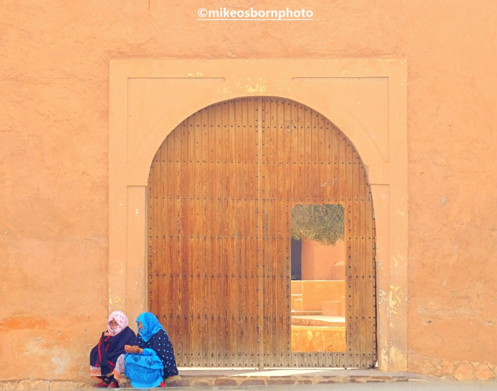 Two Moroccan women at old gate in Tiznit, Morocco