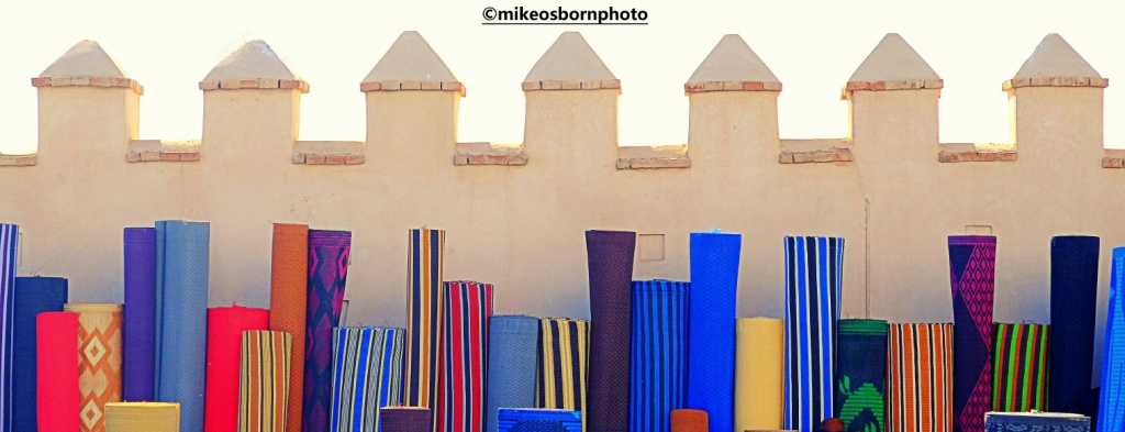 Fabric piled up against a wall of Agadir souk, Morocco