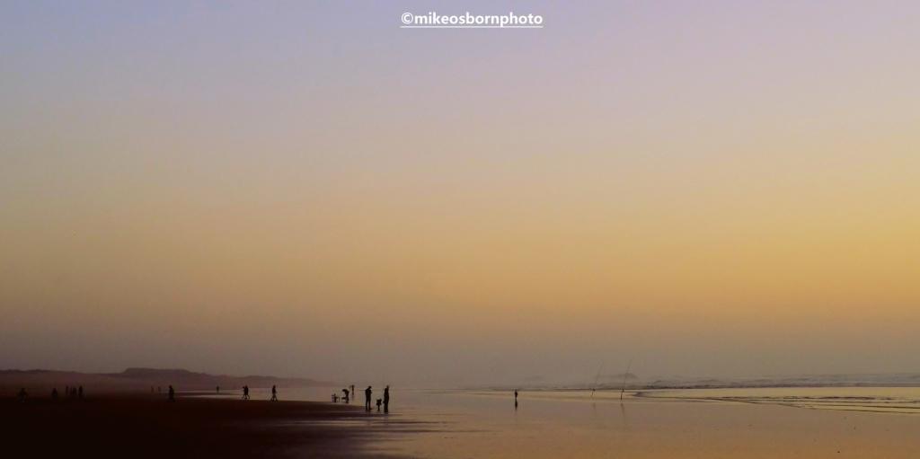 Figures on Agadir beach, Morocco at dusk