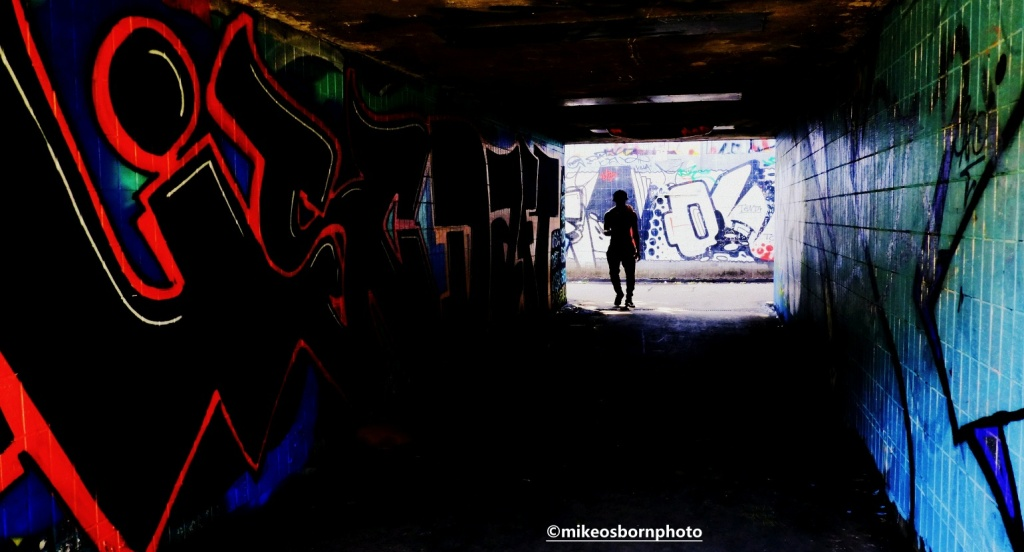 Pedestrian walks through underpass at Mancunian Way, Manchester