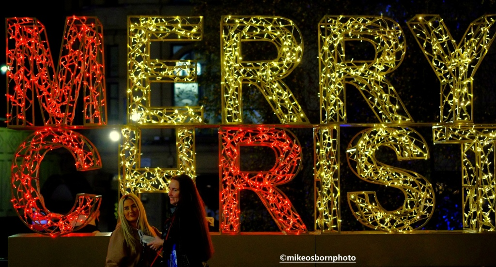 Women pose for photos at Christmas lights in Manchester
