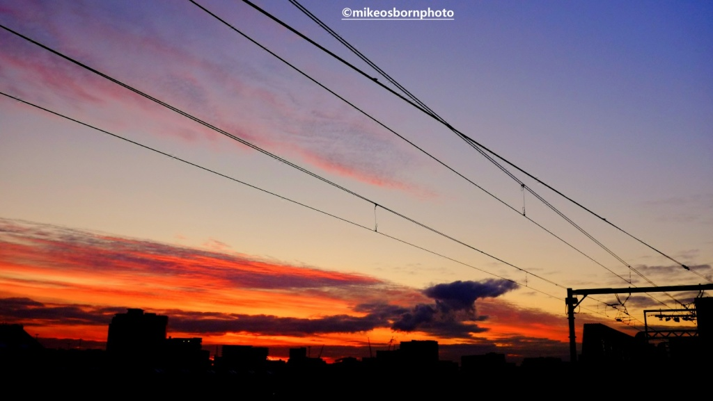 Tram lines and rooftops at sunset in Manchester