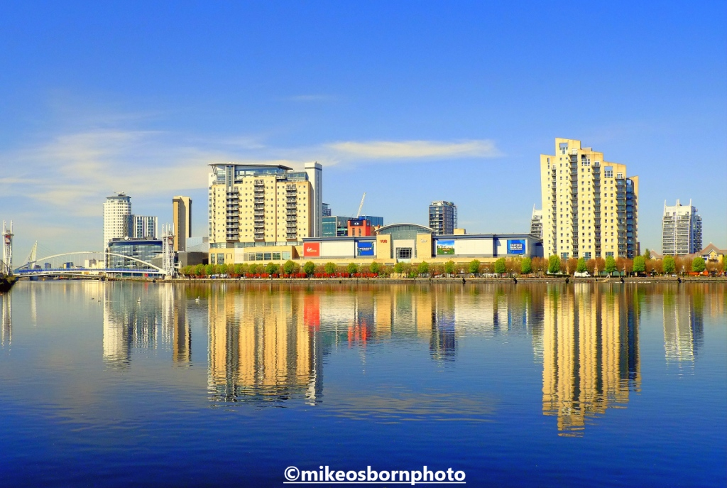 The buildings of Salford Quays reflected in the blue waters of the Manchester Ship Canal