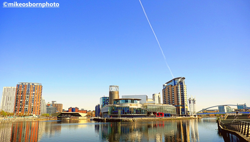 The Lowry Theatre and Salford Quays buildings reflected in the Manchester Ship Canal