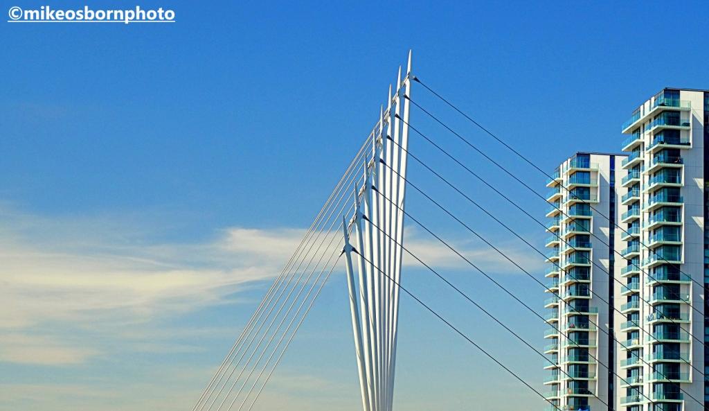 MediaCity footbridge and apartment blocks against a blue sky