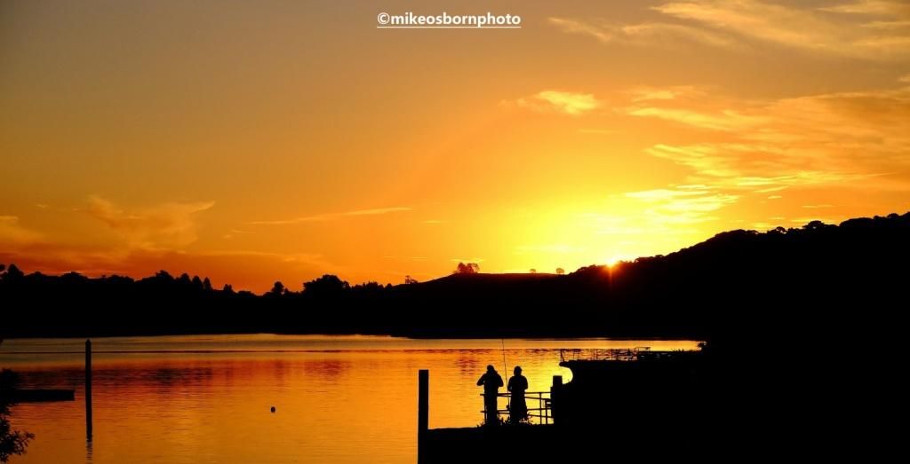 Golden sunset at Waitangi in New Zealand captures two fishermen