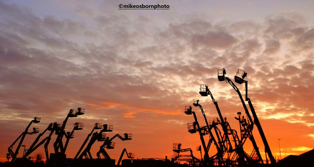 Cherry pickers at sunset in Salford