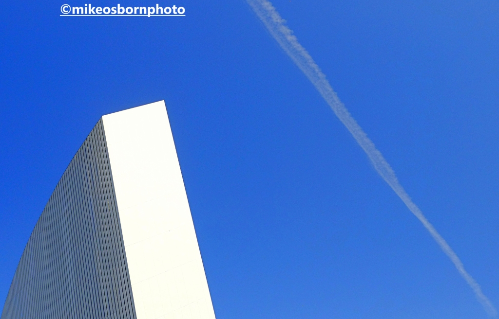 The Imperial War Museum North against a blue sky scratched by an airplane trail