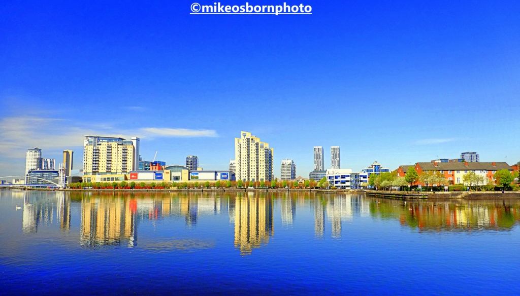 Buildings of Salford Quays reflected in blue waters of the Manchester Ship Canal
