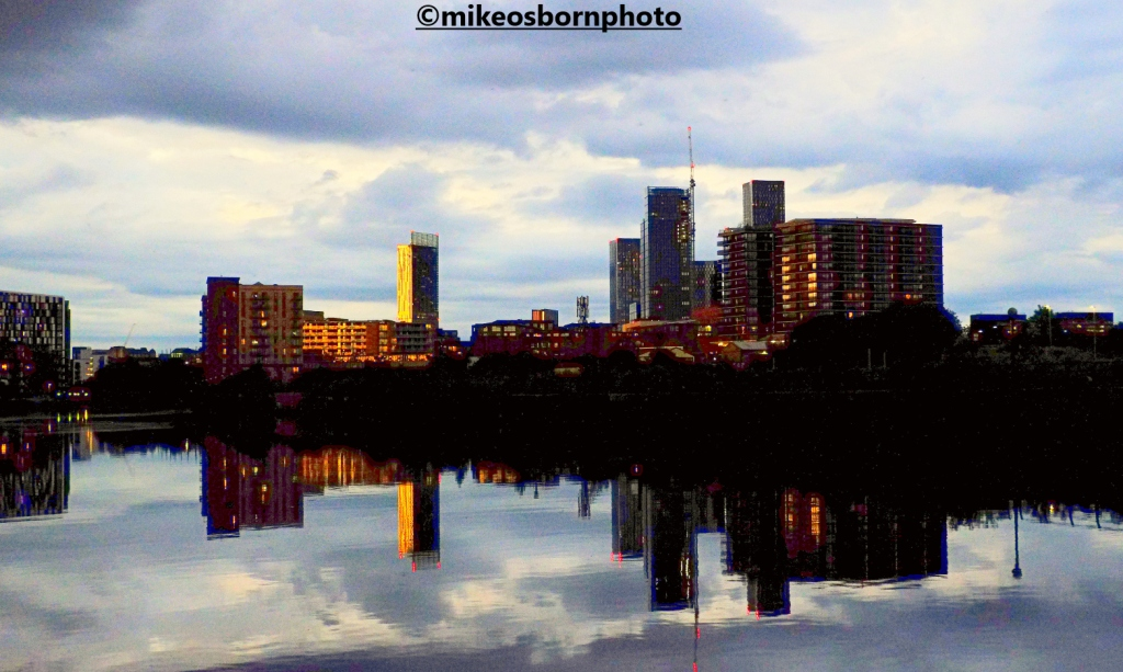 The skyline of new buildings in Manchester reflected in the Ship Canal