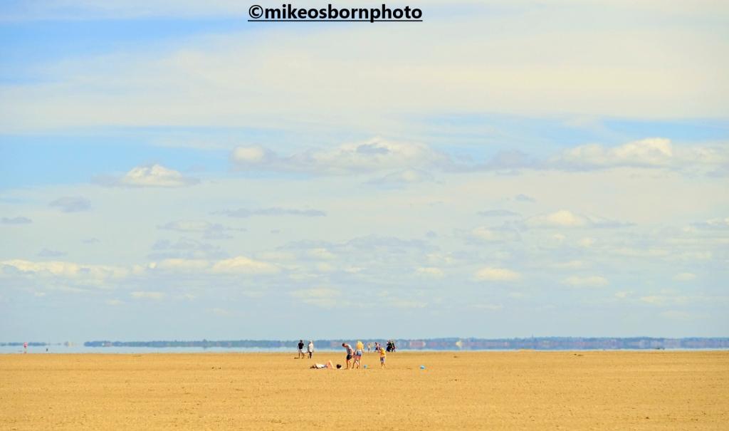 Beachgoers on the vast sands of Hoylake beach, Wirral