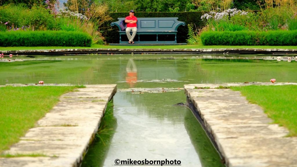 A visitor at Bodnant Garden, Wales enjoys resting on a bench
